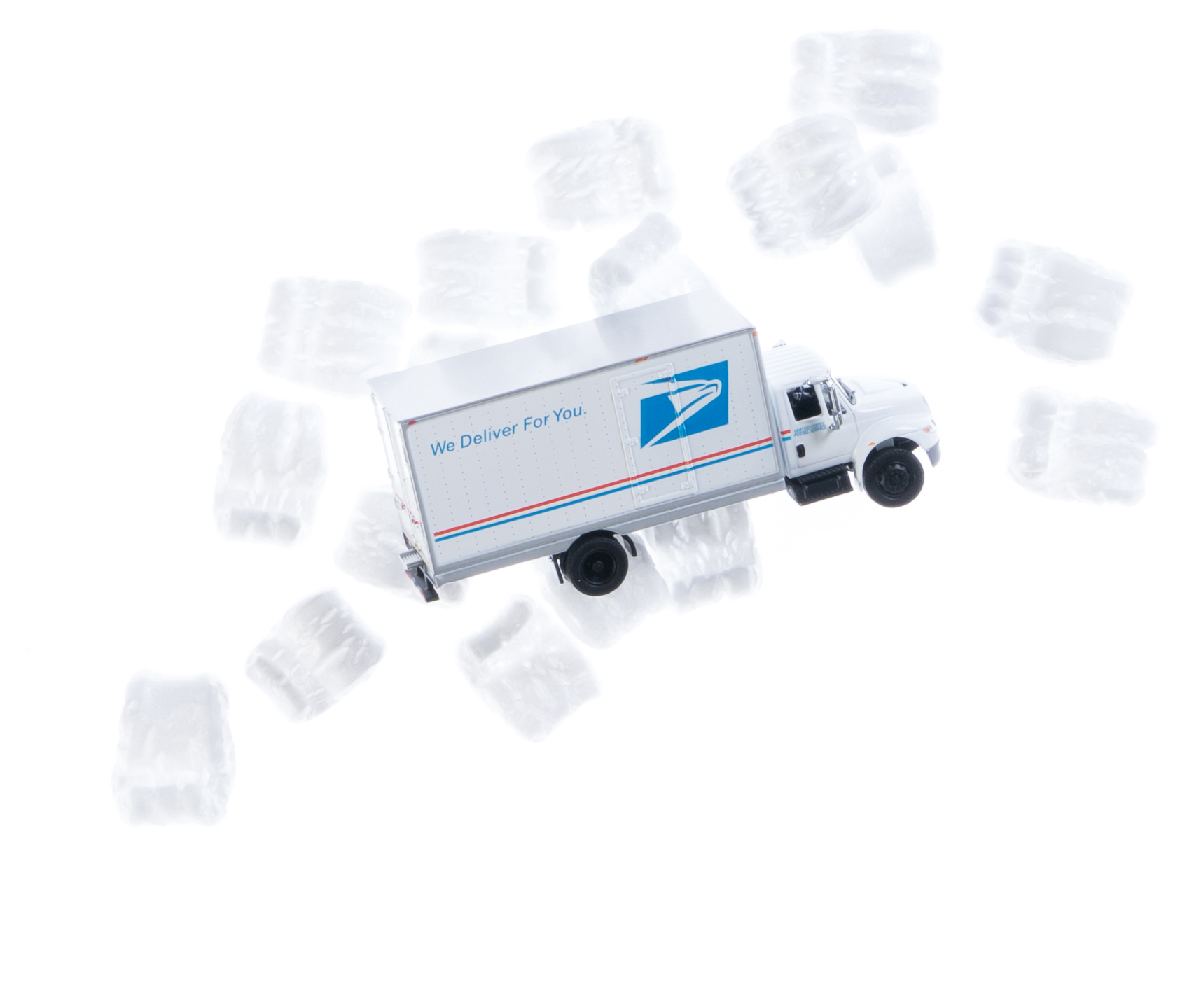 Toy commercial USPS truck plus shipping peanuts