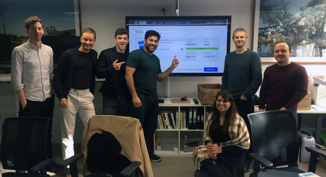 Wrisk staff infront of a screen showing their crowdfunding raise on Seedrs