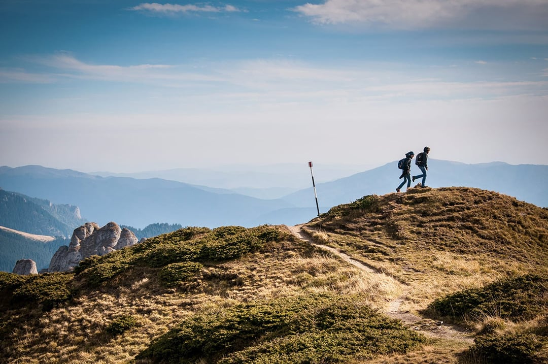 Two people walking on the mountain side