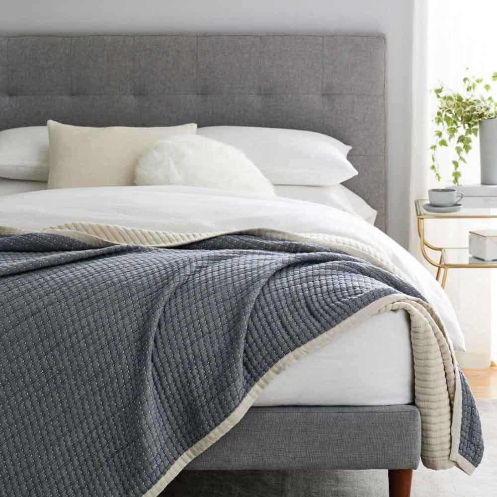 West Elm blanket draped across the end of a bed