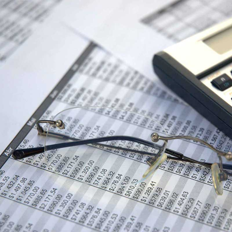 financial statements on paper with glasses and a calculator