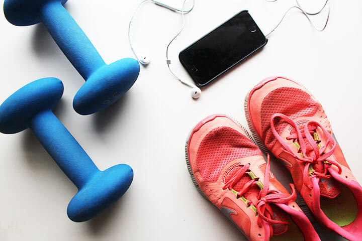 Image of fitness and exercise accessories - weights, sneakers and an iPhone with headphones
