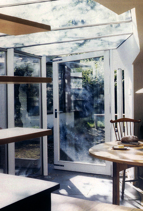 Dappled light through Ash Sakula glass birdwing canopies floods into living space and glazed door into garden.
