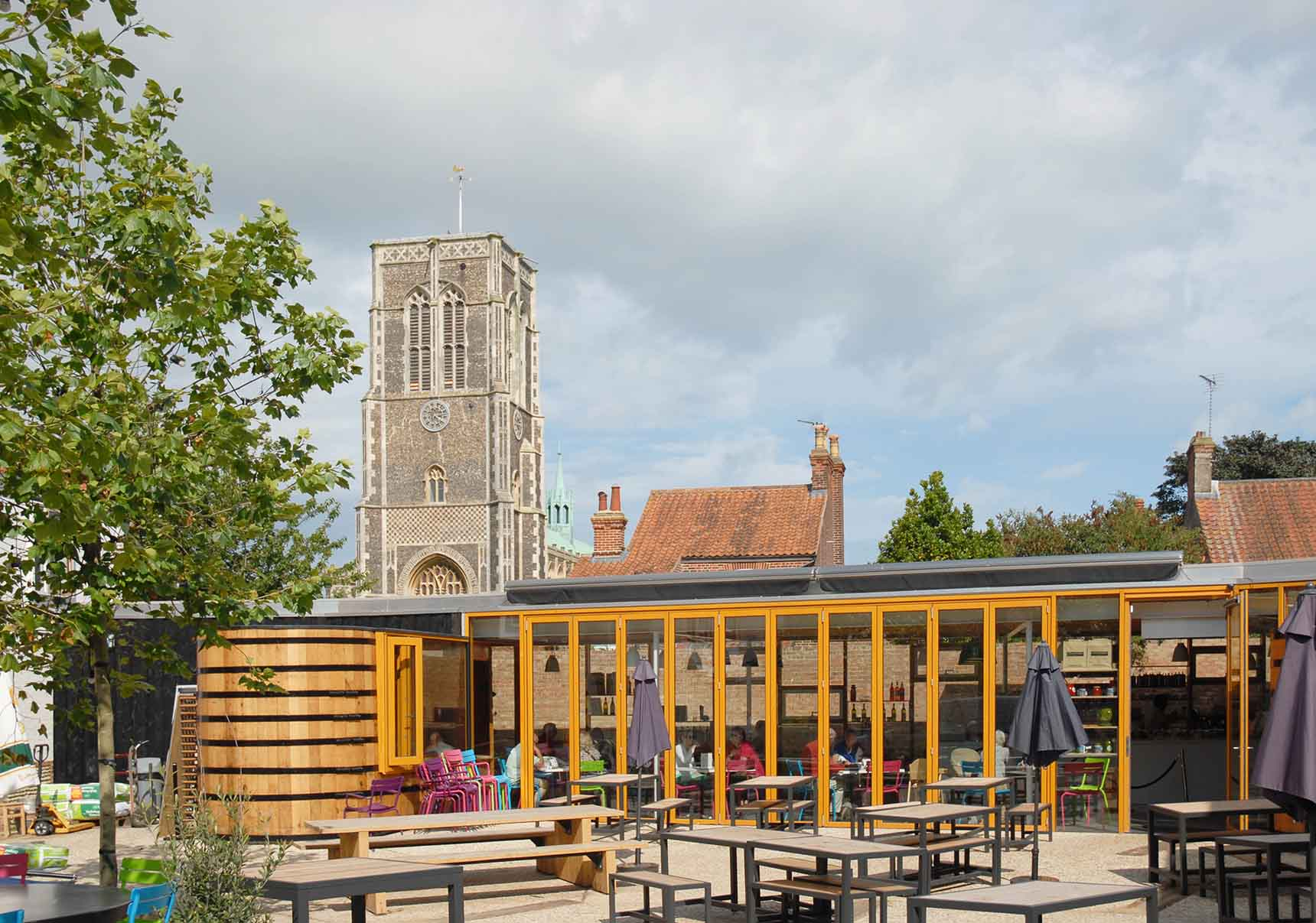 Sunny view of Drayman Square with cafe glazed wall behind and St.Edmunds Church tower in background.