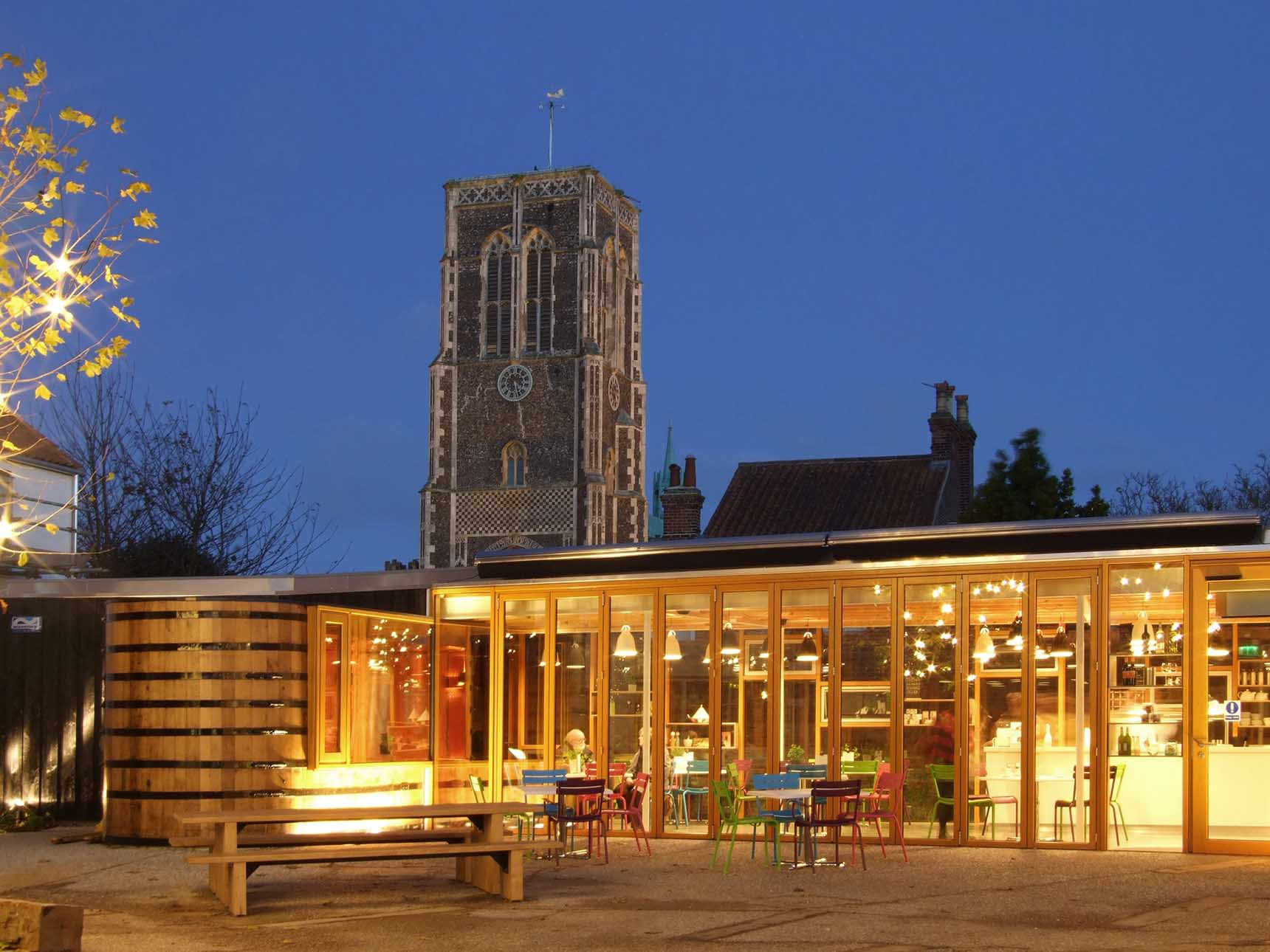 Dusk view of the warmly lit cafe with the stone church tower behind.