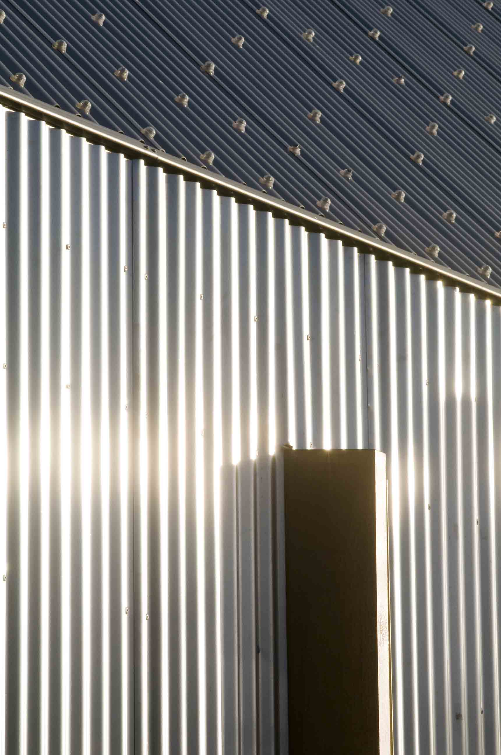 Sunlight reflecting brightly off corrugated metal cladding
