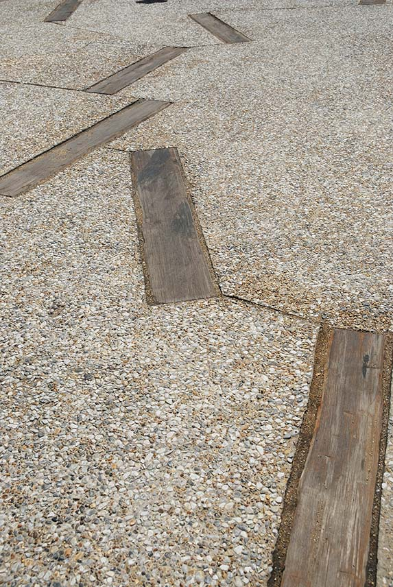 Close-up of reused weathered timber groynes set into gravel flooring.