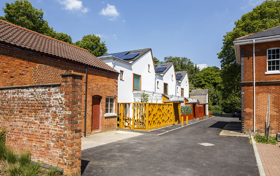 The eco-homes sit comfortably alongside historic brick dwellings to the rear of an old military fire station, now an exhibition centre for low energy housing. The new homes and stained timber fencing enliven a forgotten yard.