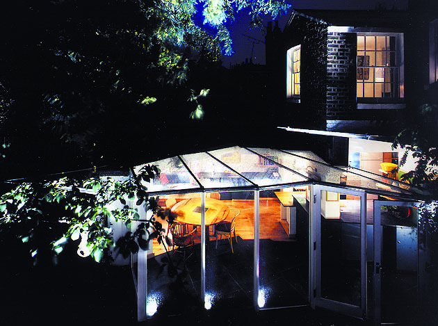 Nighttime view of Ash Sakula birdwing glass extension with warm living space inside