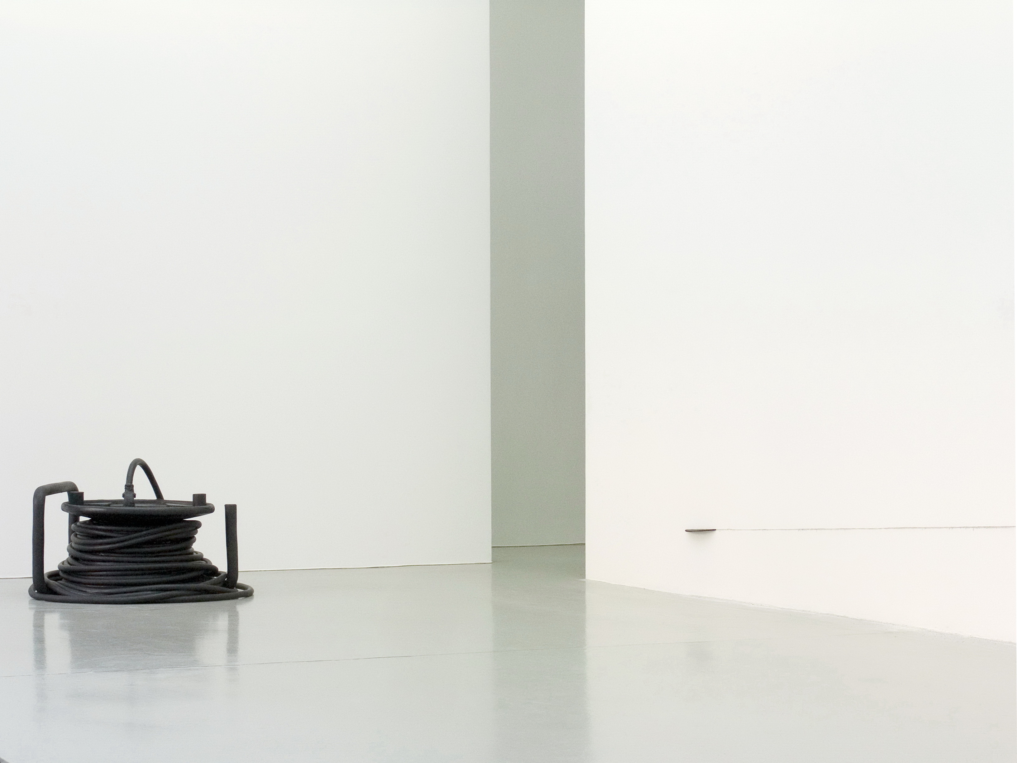 Kabeltrommel, a black oversized cabledrum sculpture made of epoxy resin by sculptor Erik Andersen. The artwork is placed on the floor of Charim Ungar Contemporary Gallery in Berlin, back in 2010