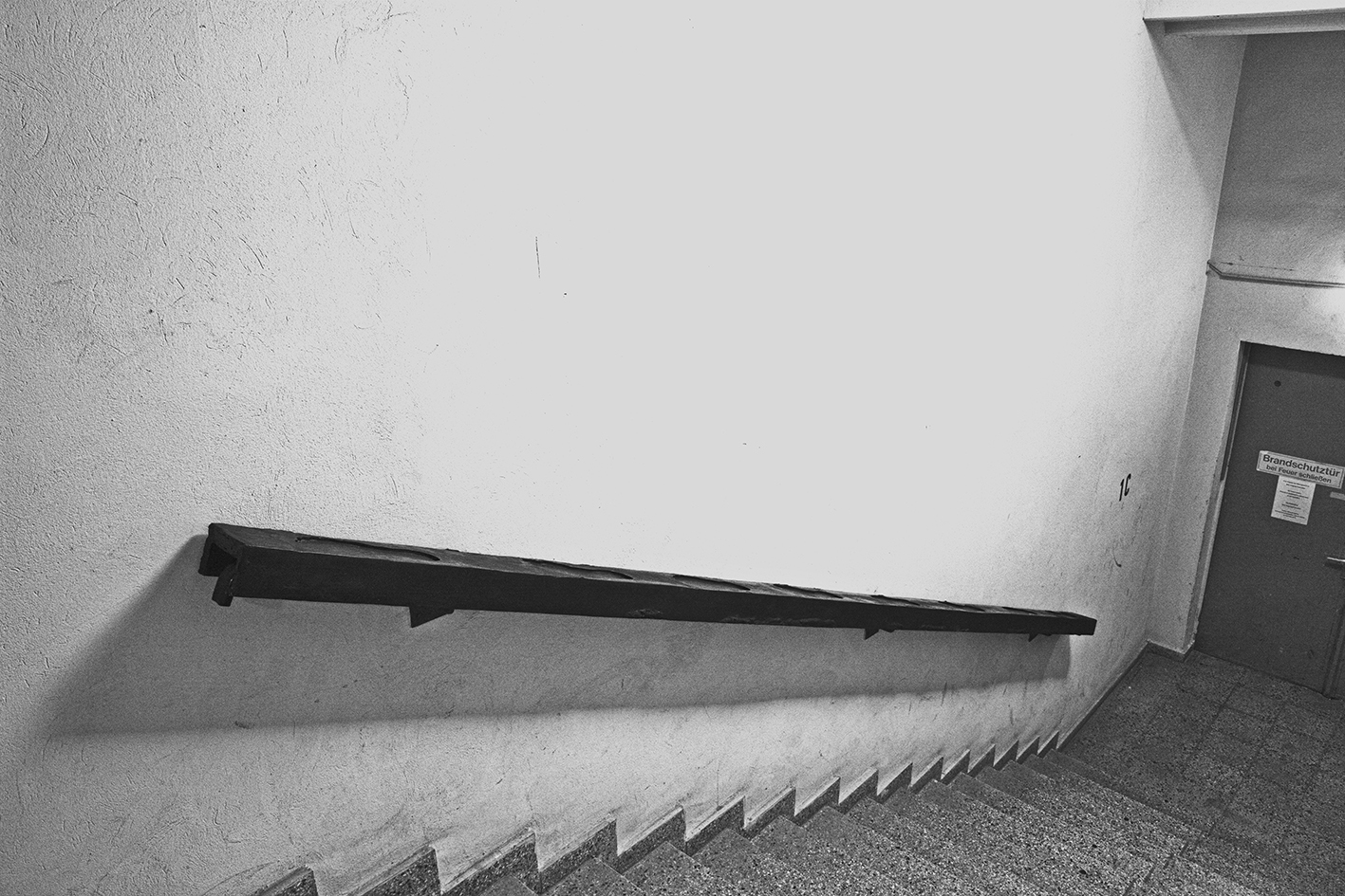 black and white photo of a staircase with a black sculpture by Erik Andersen placed on the handrail.