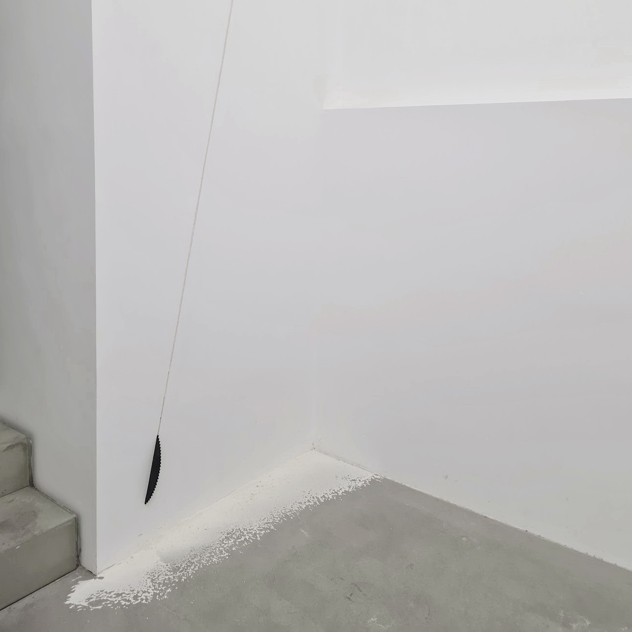 "A sawblade made of black epoxy resin is cutting the wall from behind. The dust from cutting the wall is still on the floor. ""Cut"" is an artwork by Erik Andersen."