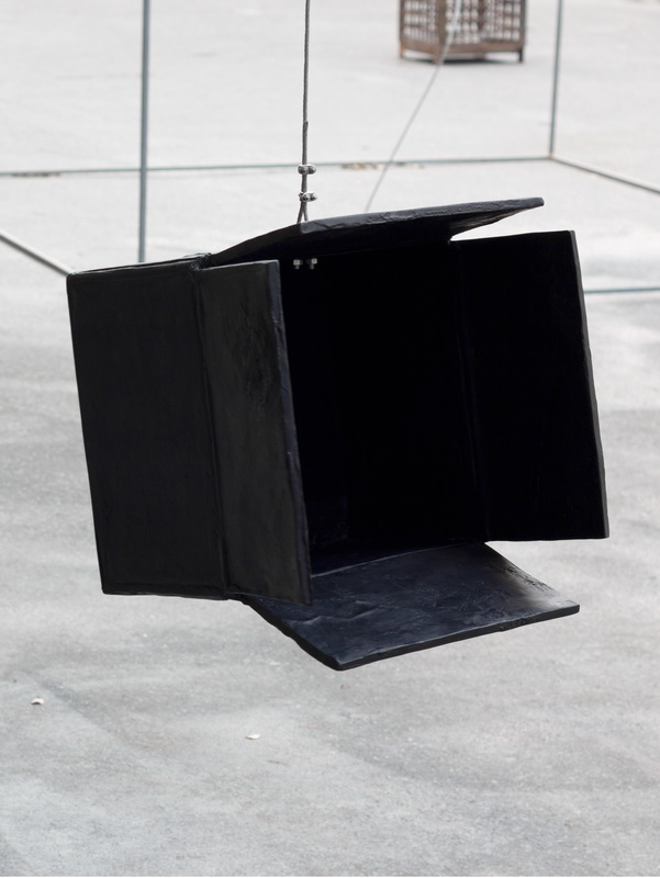 Black Hole is a sculpture made of black epoxy resin hanging on a steel rope. Here it is an installation view outside.