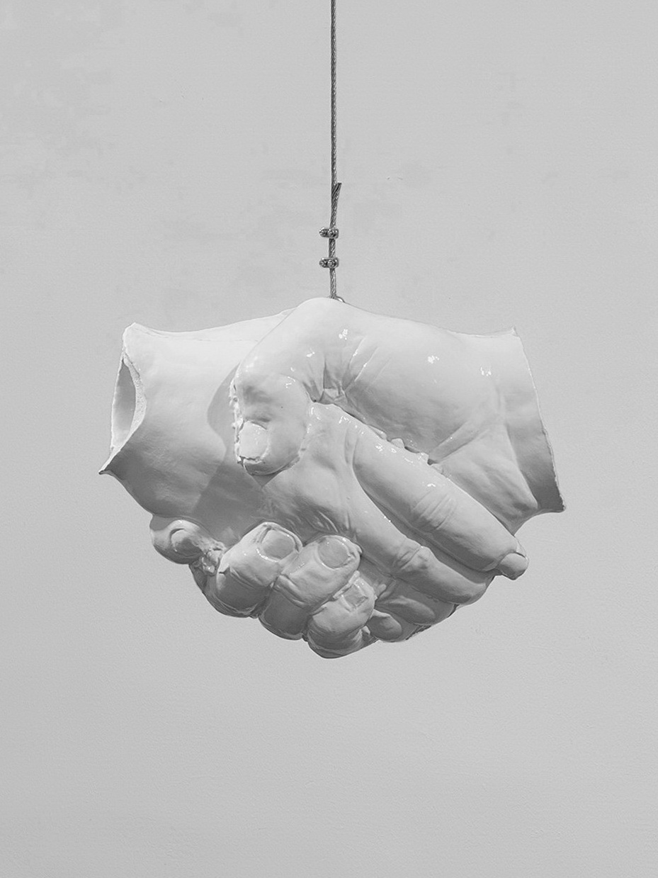 """The artwork """"Handschlag"""" is a white glazed ceramic sculpture hanging on a steel rope. This is a black and white photo."""