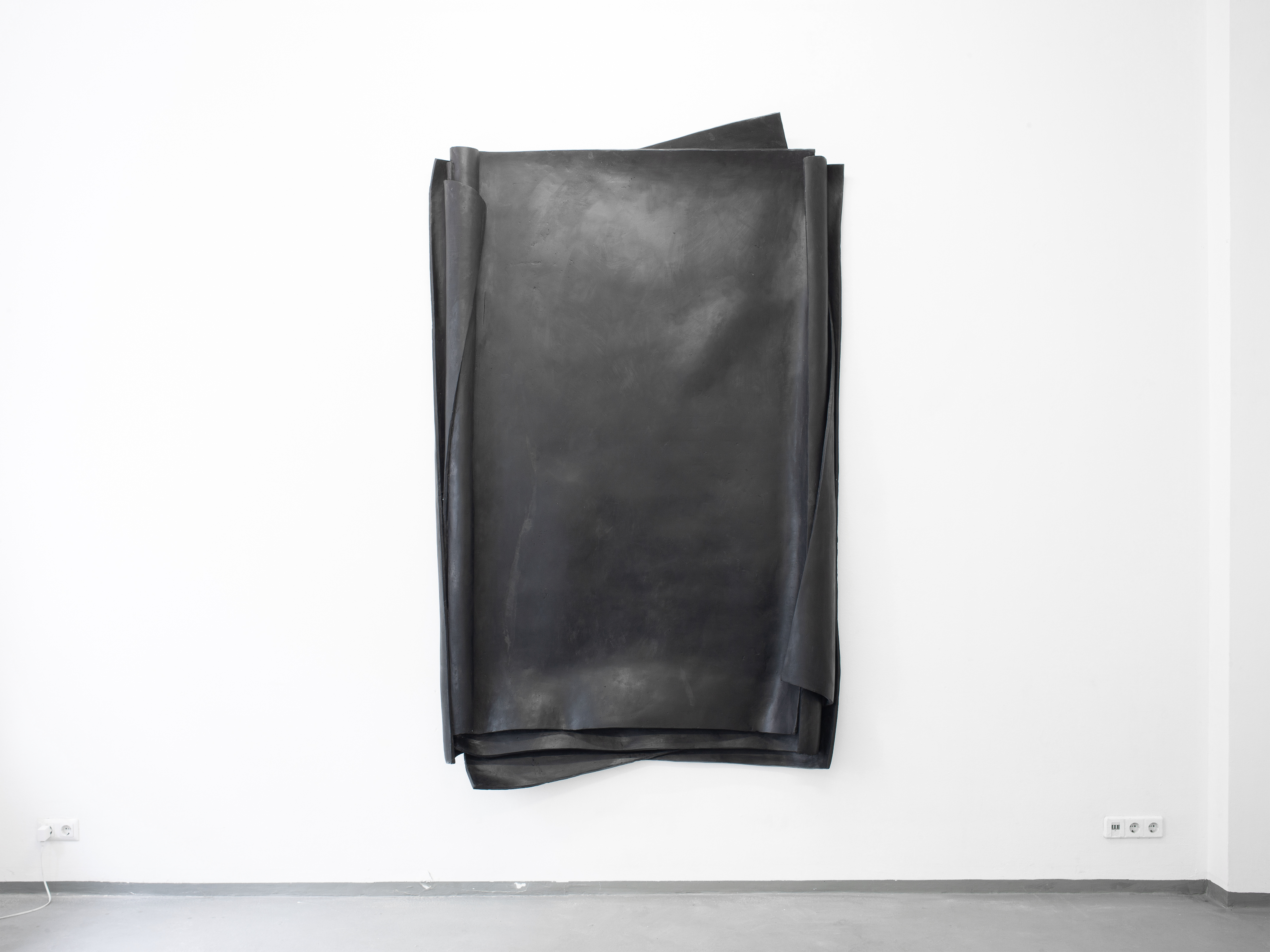 Besser Vertikal 02 is a sculpture made out of black Epoxy Resin. The artwork by Erik Andersen is presented hanging on the white wall of the gallery.