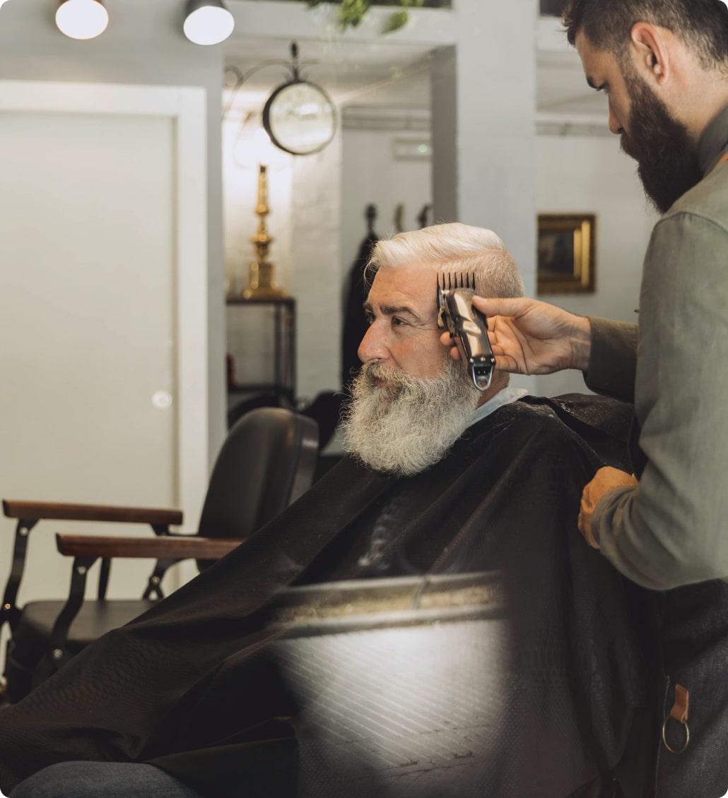 Барбер бреет пожилого мужчину