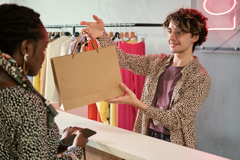 Девушка забирает покупку у продавца и очень рада жизни