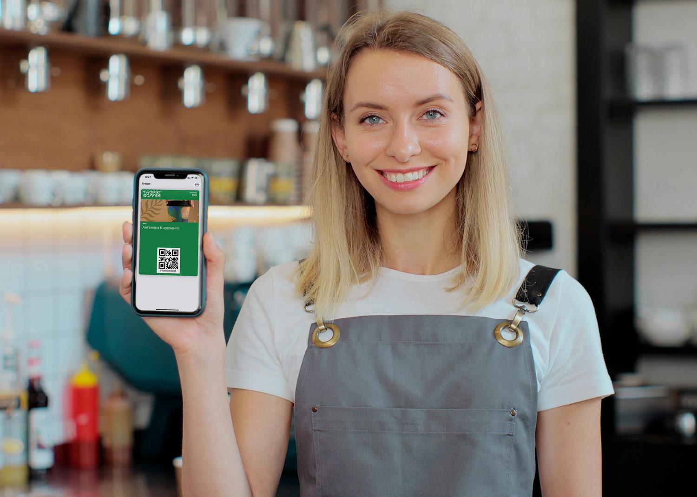 Бариста показывает электронную карту лояльности в телефоне