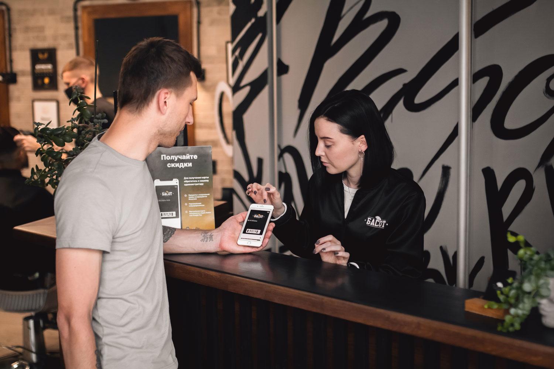Администратор салона рассказывает клиенту, как установить карту лояльности
