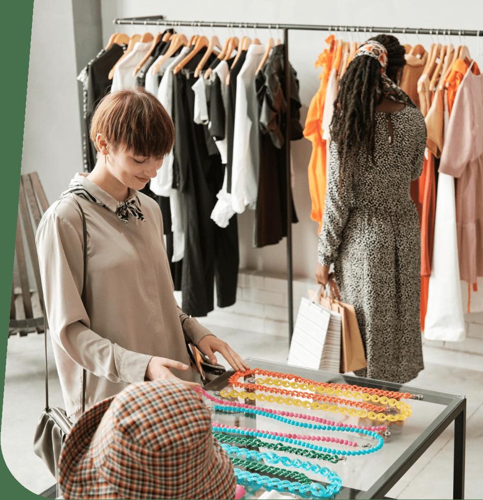 Девушки рассматривают товар в магазине одежды