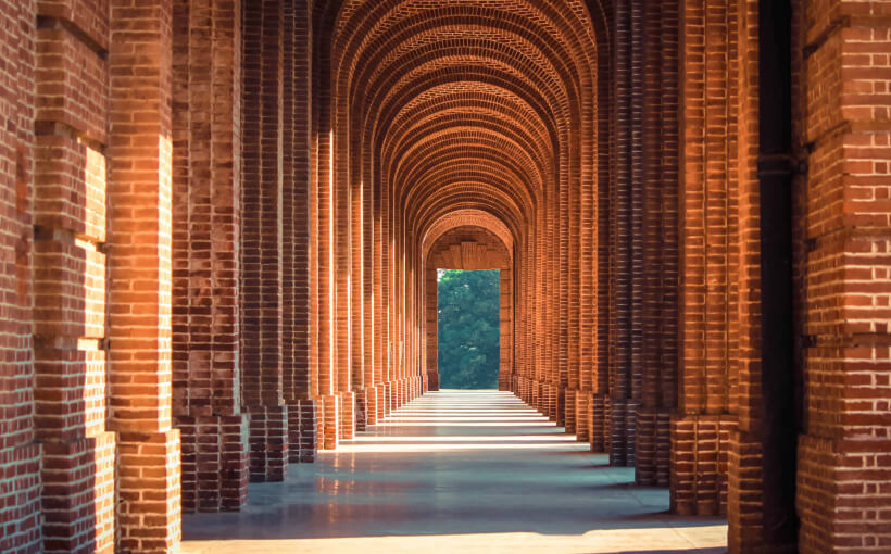 Brick columns line a sunlit campus walkway.