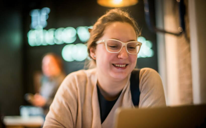 Sasha wears glasses and sits smiling at her laptop in front of neon green lights.