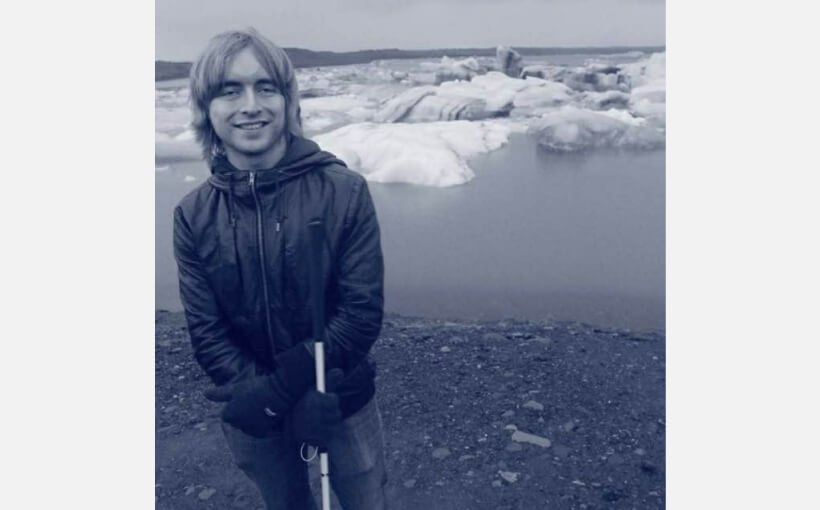 Warren stands before ice-covered water wearing a windbreaker, white cane in hand.