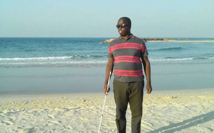 Paul standing on a beach, holding his white cane.