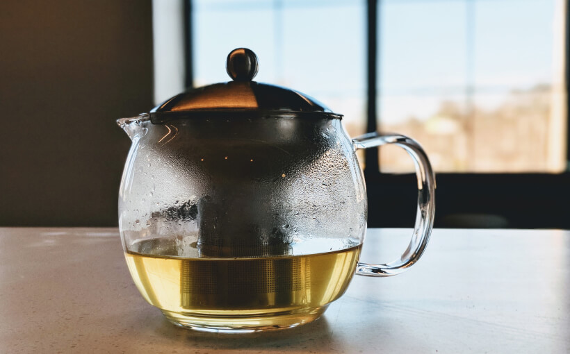 A pot of tea placed on a kitchen counter.