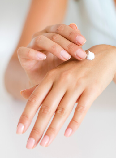 Female spreading lotion on the back of one of her hands