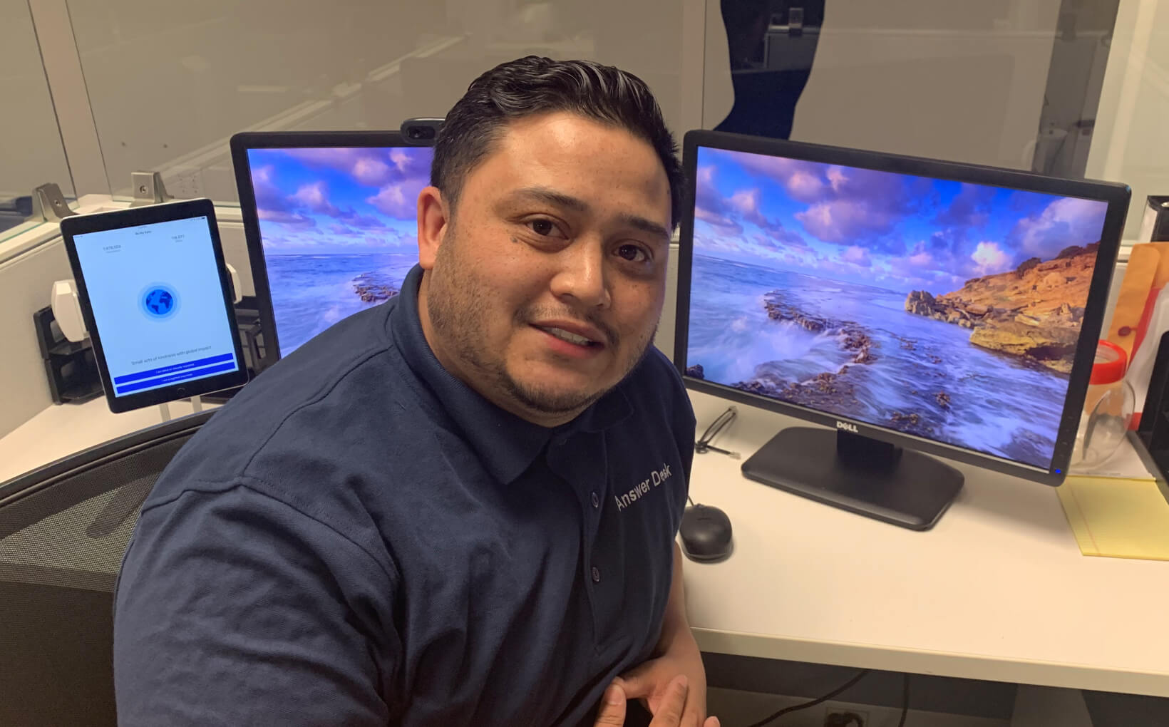 Mike sitting in front of his desk at the Microsoft Disability Answer Desk. He's turned towards the camera, smiling. On his desk is his desktop computer and a tablet with be My Eyes open.