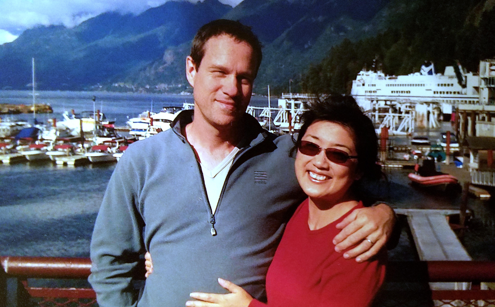 Yuki standing at a harbour with her husband. They are both smiling to the camera and embracing each other.