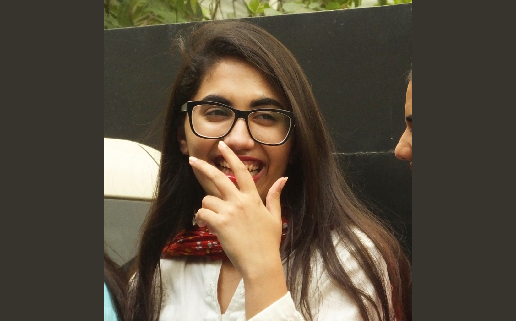 Photo of Nawaal. She has long brown hair, and she's wearing a white shirt, a red scarf, black glasses, and red lipstick. She's holding up her hand to cover her mouth as she laughs.