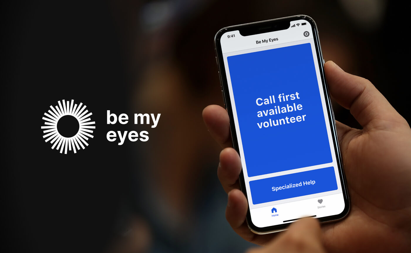 Hand-held iPhone with the Be My Eyes app presenting blind user's home screen with two buttons: 'Call first available volunteer' and 'Specialized Help'.