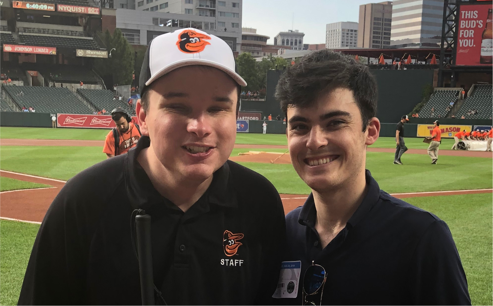 Bryce posing with a friend on a baseball field. Bryce is wearing a cap and a t-shirt with the Baltimore Oriole logo.