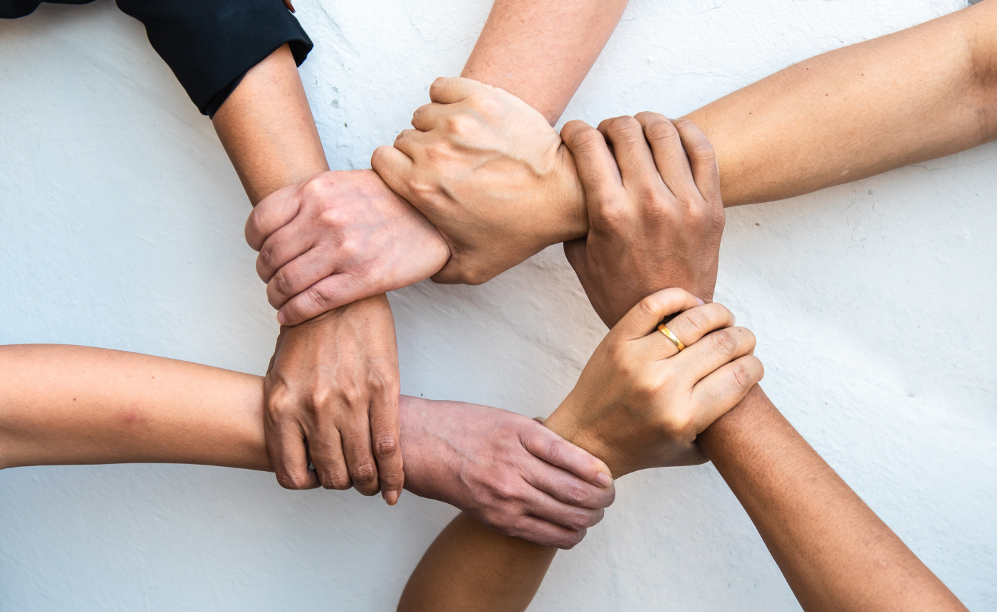 Six hands holding on to each other's wrists, forming a circle