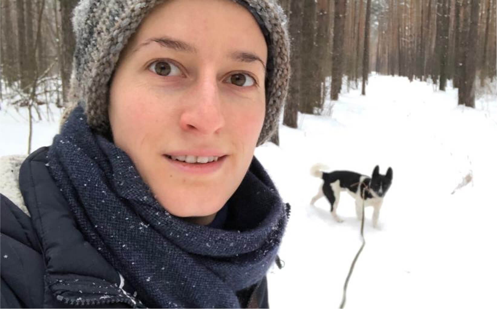 Daria takes a selfie while walking a dog in the snow