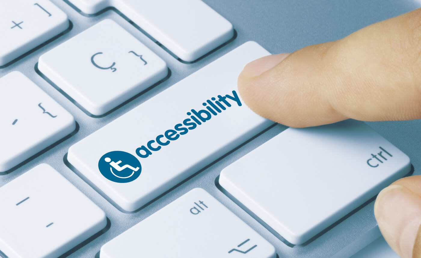 """Finger pressing key on a computer keyboard saying """"accessibility""""."""