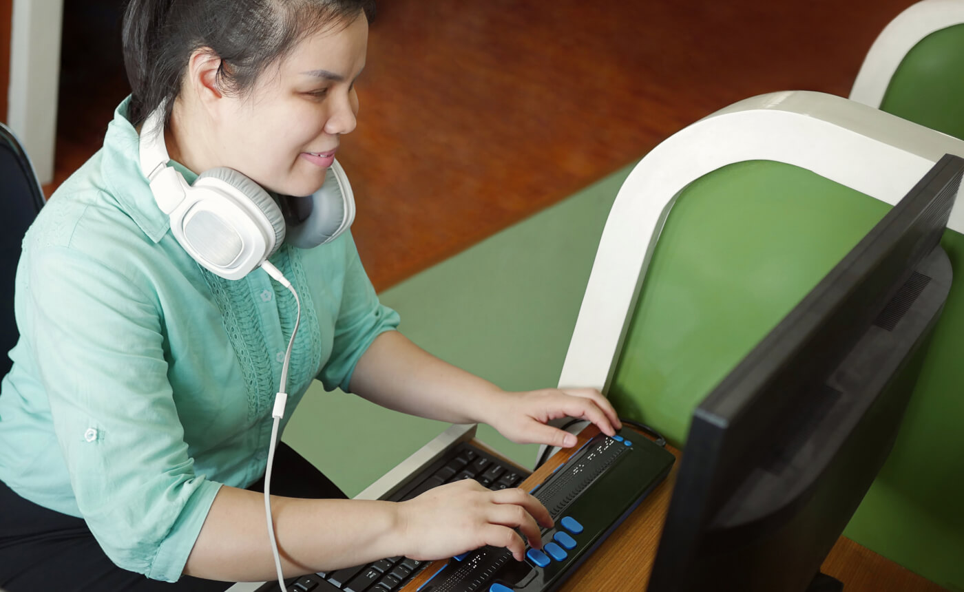 Woman works on a computer with a braille keyboard.
