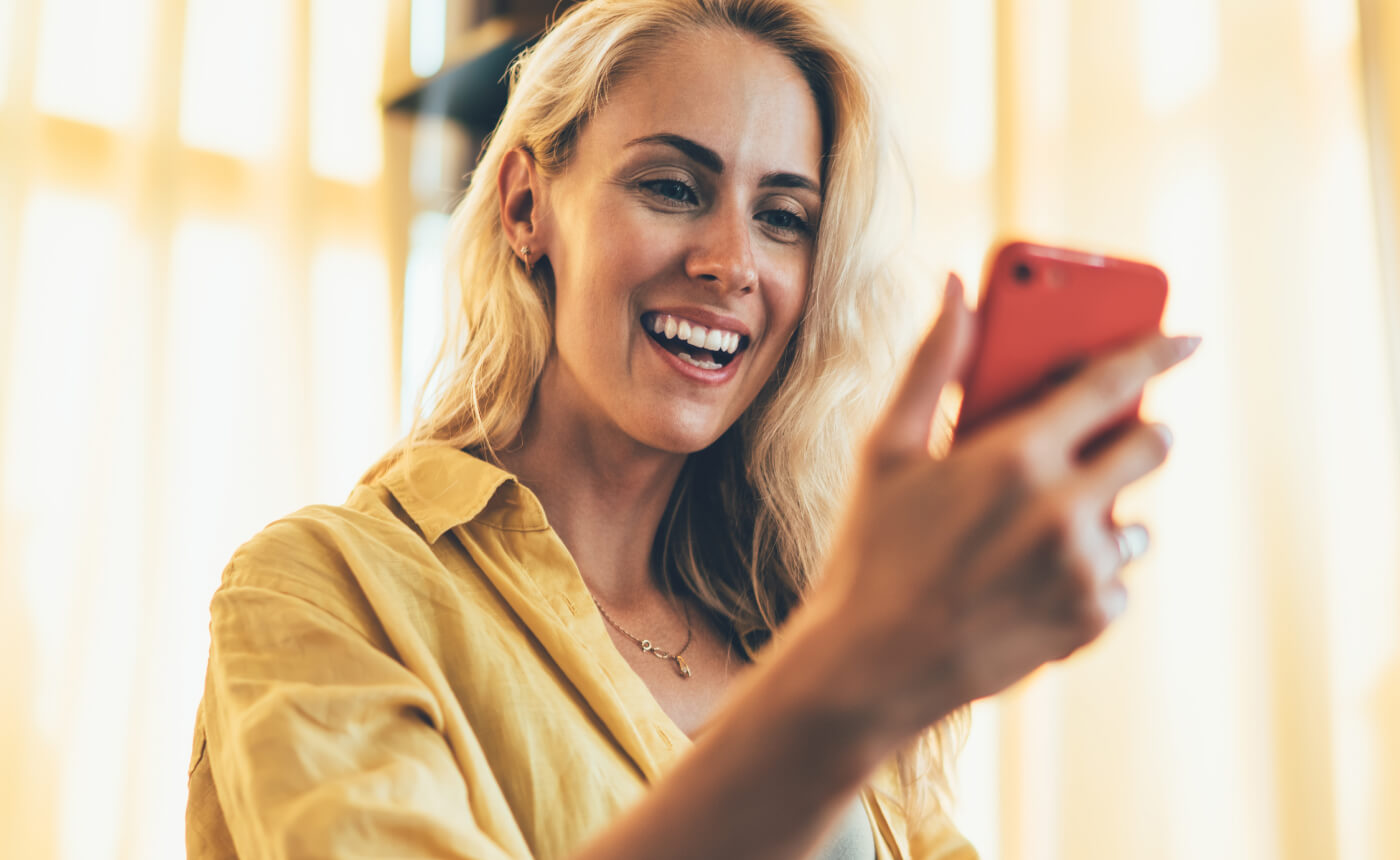 Woman smiling while on a video call on her smartphone.