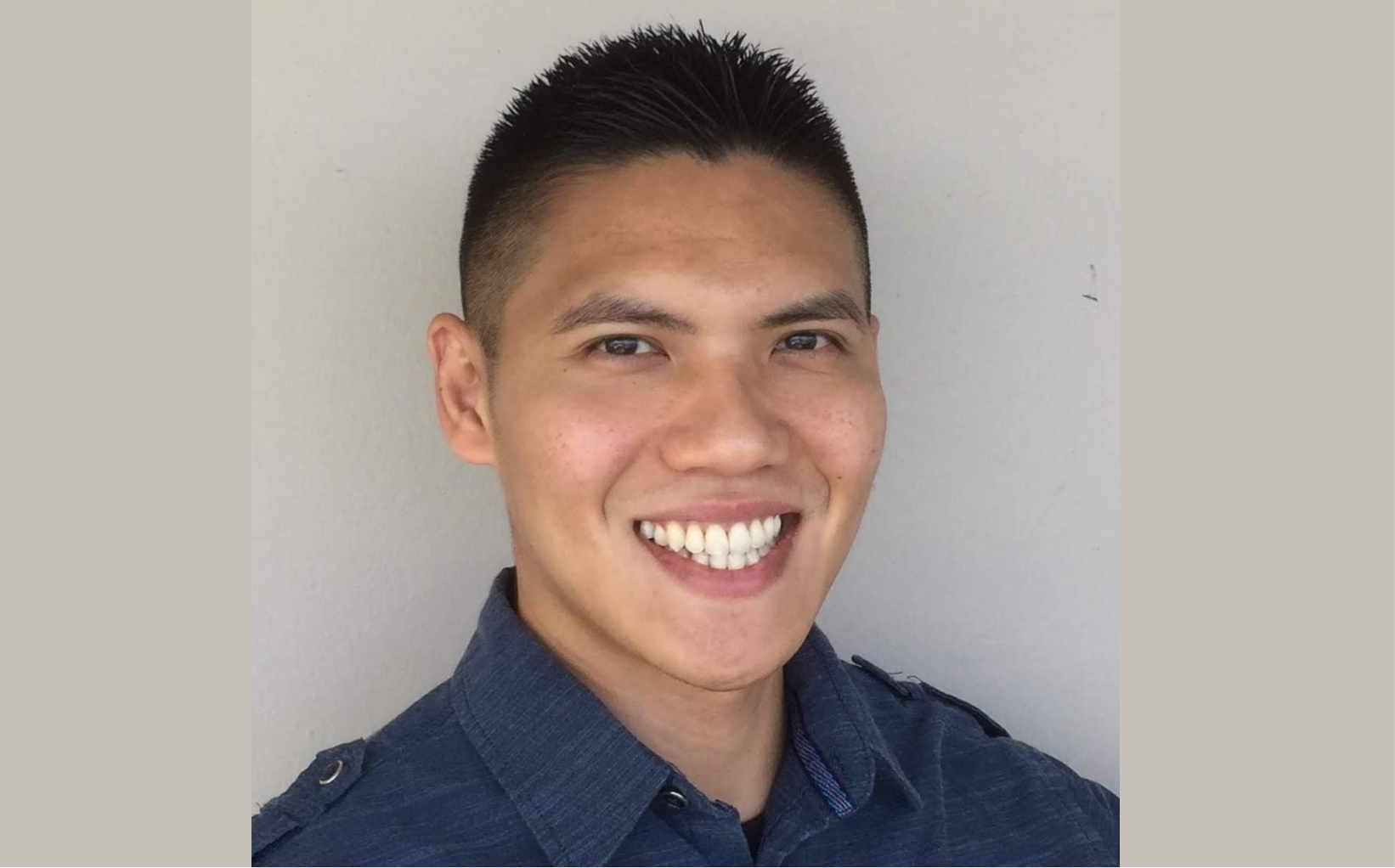 Derek, wearing a navy shirt, smiling to the camera.