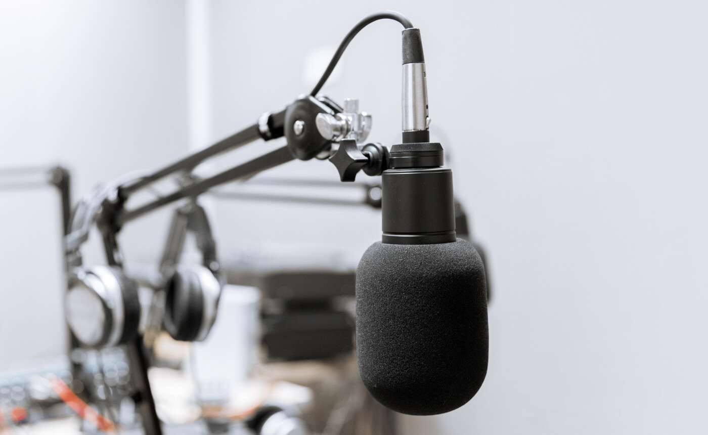 Photo of a podcast microphone with other recording equipment in the background.