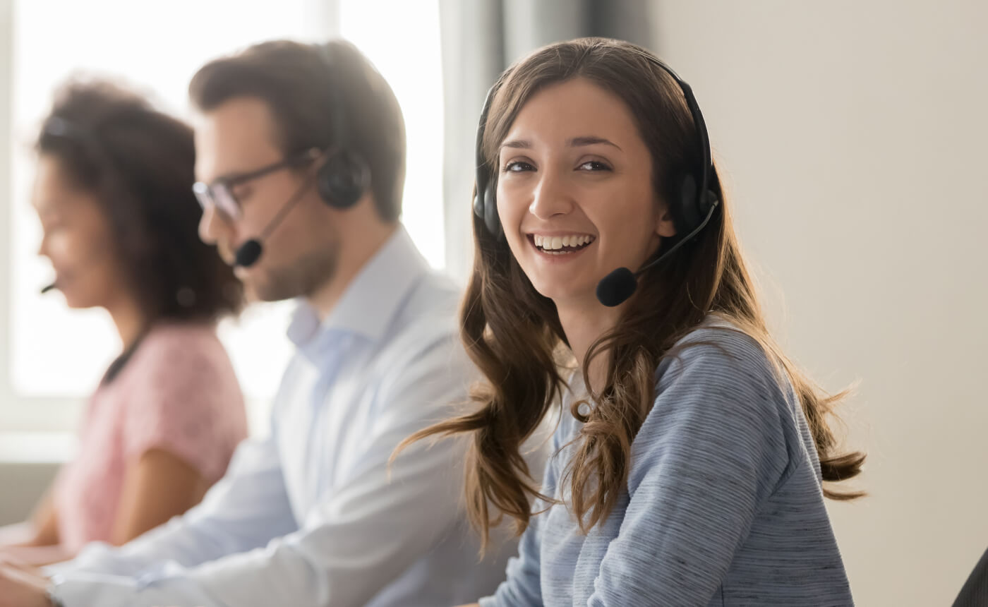 Female customer support employee wearing a headset is looking sideways and smiling to the camera. Behind her, two of her colleagues are talking on their headsets.