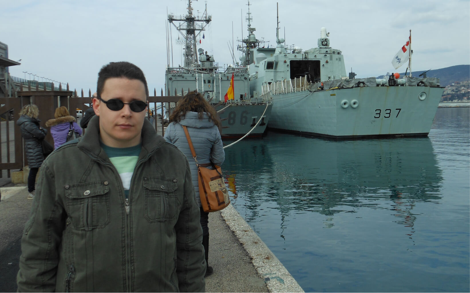 Milos standing at a harbor front with two large ships behind him.