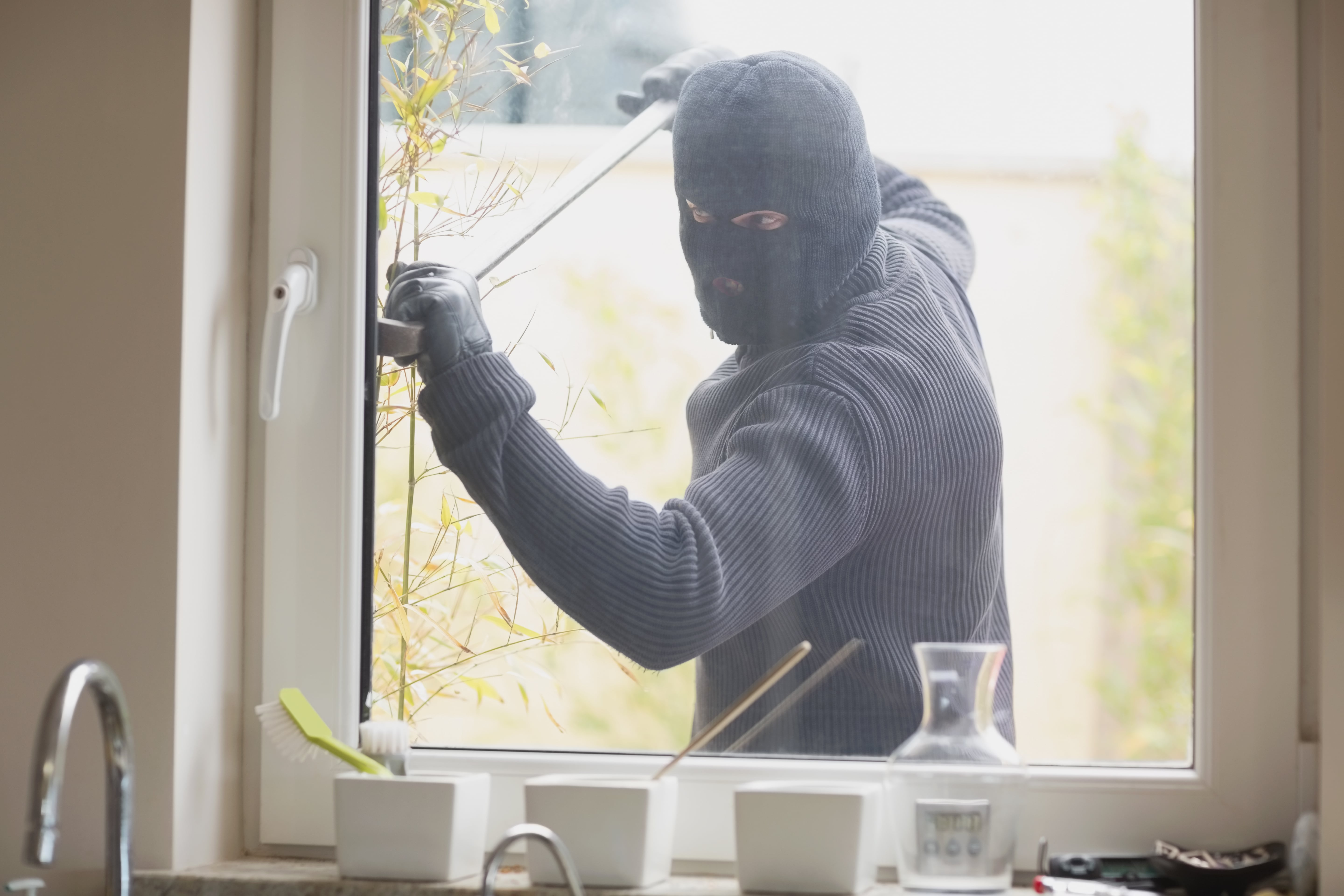 robber breaking into home without security film