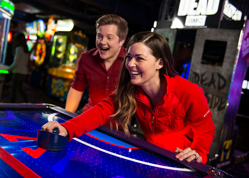 Girl and boy playing air hockey in arcade