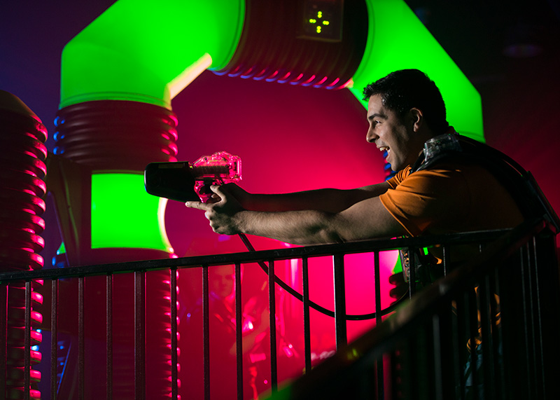 Man posing for picture in a laser tag arena