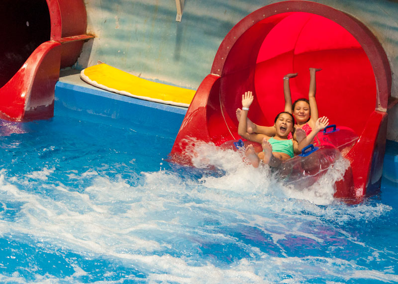 Girls sliding down red waterslide