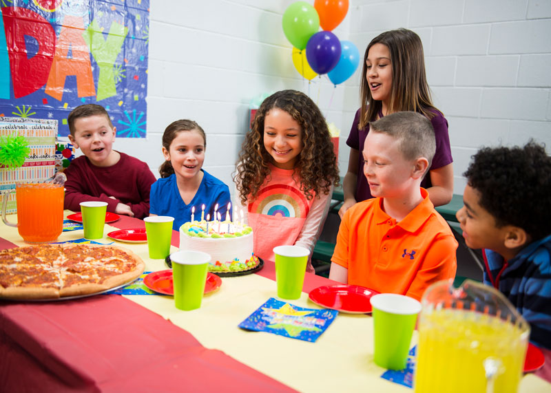 Kids celebrating birthday party with cake and pizza