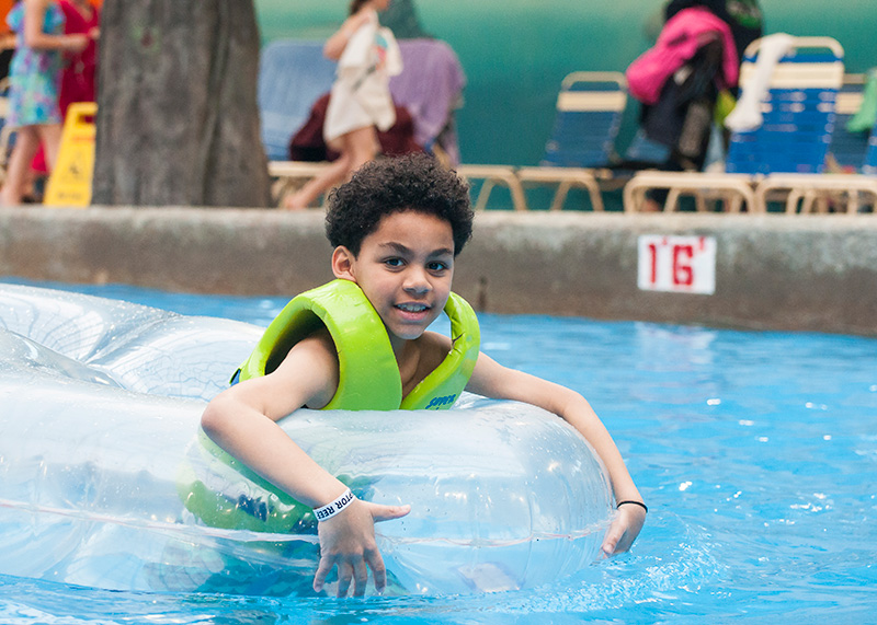 Young boy in an inner tube in a pool